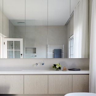 Photo of a contemporary bathroom in Melbourne with flat-panel cabinets, light wood cabinets, a freestanding tub, beige tile, beige walls, an undermount sink, beige floor and white benchtops.