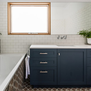 Design ideas for a mid-sized contemporary master bathroom in Melbourne with shaker cabinets, blue cabinets, a drop-in tub, a one-piece toilet, white tile, porcelain tile, white walls, porcelain floors, an undermount sink, engineered quartz benchtops and brown floor.