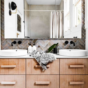 Design ideas for an eclectic bathroom in Melbourne with flat-panel cabinets, light wood cabinets, gray tile, white walls, a vessel sink and white benchtops.