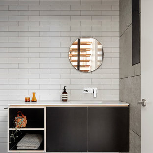 Contemporary bathroom in Melbourne with flat-panel cabinets, black cabinets, white walls and an integrated sink.