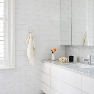 Mid-sized contemporary master bathroom in Melbourne with white cabinets, white tile, subway tile, white walls, marble floors, an undermount sink, marble benchtops, grey floor and flat-panel cabinets.