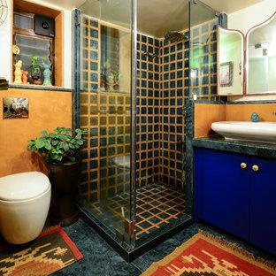 Cette photo montre une salle d'eau éclectique avec un placard à porte plane, des portes de placard bleues, une douche d'angle, un WC à poser, un mur orange, une vasque, un sol bleu, une cabine de douche à porte battante et un plan de toilette bleu.