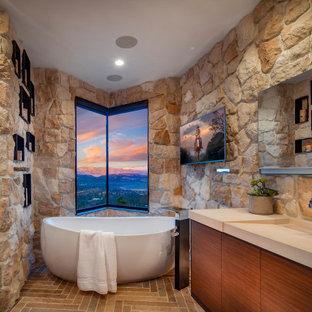 Modelo de cuarto de baño principal, rústico, con armarios con paneles lisos, puertas de armario de madera oscura, bañera exenta, baldosas y/o azulejos de piedra, lavabo integrado, encimeras beige y suelo multicolor