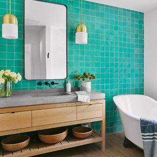 Modelo de cuarto de baño actual con armarios con paneles lisos, puertas de armario de madera clara, bañera exenta, baldosas y/o azulejos azules, paredes blancas, suelo de madera clara, lavabo integrado, encimera de cemento, suelo beige y encimeras grises