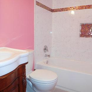 Imagen de cuarto de baño con ducha, bohemio, de tamaño medio, con armarios tipo mueble, puertas de armario de madera oscura, bañera empotrada, combinación de ducha y bañera, sanitario de dos piezas, paredes rosas, suelo de baldosas de cerámica y lavabo integrado