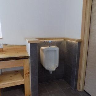 На фото: с высоким бюджетом ванные комнаты среднего размера в стиле лофт с фасадами островного типа, светлыми деревянными фасадами, открытым душем, писсуаром, белыми стенами, полом из галечной плитки, душевой кабиной, накладной раковиной, столешницей из дерева, серым полом, душем с раздвижными дверями и коричневой столешницей