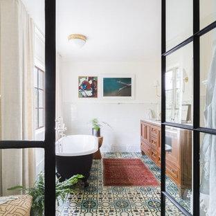 Inspiration pour une salle de bain principale traditionnelle avec un placard à porte shaker, des portes de placard en bois brun, une baignoire indépendante, un mur beige et un sol turquoise.