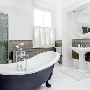 На фото: главная ванная комната в стиле современная классика с ванной на ножках, угловым душем, серой плиткой, белыми стенами, деревянным полом и раковиной с пьедесталом с