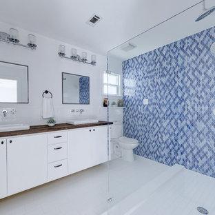 Modelo de cuarto de baño marinero con armarios con paneles lisos, puertas de armario blancas, ducha doble, sanitario de dos piezas, baldosas y/o azulejos en mosaico, paredes azules, lavabo sobreencimera, encimera de madera, suelo blanco, ducha abierta y encimeras marrones