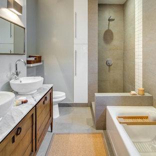 Modelo de cuarto de baño actual con armarios tipo mueble, puertas de armario de madera oscura, bañera esquinera, ducha esquinera, baldosas y/o azulejos grises, paredes grises, lavabo sobreencimera, suelo gris, ducha abierta y encimeras grises