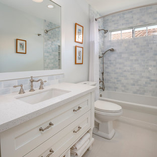 Transitional blue tile and white tile beige floor bathroom photo with beaded inset cabinets, white cabinets, a two-piece toilet, white walls and an undermount sink