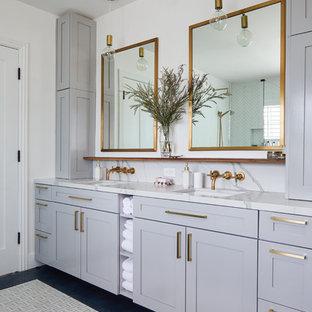 Imagen de cuarto de baño principal, tradicional renovado, con armarios estilo shaker, puertas de armario grises, paredes blancas, lavabo bajoencimera, suelo negro y encimeras blancas