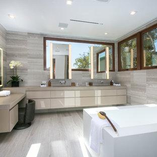 Esempio di una stanza da bagno padronale minimalista con ante lisce, ante beige, vasca da incasso, piastrelle grigie, piastrelle di pietra calcarea, pareti grigie, lavabo sottopiano e pavimento grigio