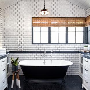 Exemple d'une grand salle de bain principale bord de mer avec un placard à porte shaker, des portes de placard blanches, une baignoire indépendante, un carrelage jaune, un carrelage métro, un sol en carrelage de porcelaine, un sol noir, un plan de toilette gris, meuble double vasque, meuble-lavabo encastré et un plafond en lambris de bois.