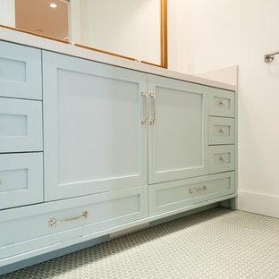 Imagen de cuarto de baño con ducha, de estilo de casa de campo, pequeño, con puertas de armario azules, combinación de ducha y bañera, paredes blancas, suelo de madera en tonos medios y lavabo sobreencimera