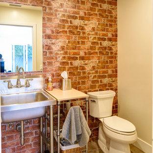Immagine di una stanza da bagno con doccia industriale di medie dimensioni con ante grigie, piastrelle rosse, lastra di pietra, pareti rosse, pavimento in travertino, lavabo a colonna e top in acciaio inossidabile