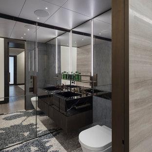 Esempio di una stanza da bagno design di medie dimensioni con ante lisce, ante nere, doccia alcova, WC sospeso, piastrelle a specchio, pavimento con piastrelle a mosaico, lavabo integrato, pavimento multicolore e porta doccia scorrevole