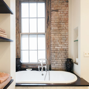 Design ideas for an urban ensuite bathroom in New York with open cabinets, a built-in bath and white walls.