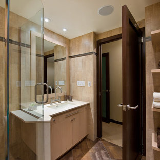Corner shower - mid-sized contemporary 3/4 porcelain tile and brown floor corner shower idea in New York with flat-panel cabinets, light wood cabinets, beige walls, an undermount sink, solid surface countertops and a hinged shower door