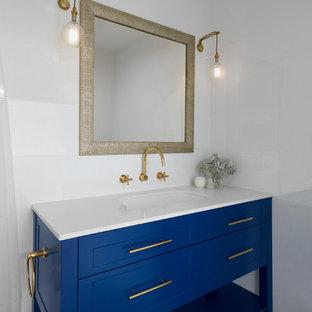 Modelo de cuarto de baño con ducha, tradicional, de tamaño medio, con armarios tipo mueble, puertas de armario azules, bañera exenta, baldosas y/o azulejos blancos, paredes blancas, suelo con mosaicos de baldosas, lavabo integrado, encimera de laminado, suelo multicolor y encimeras blancas