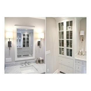 Klassisk inredning av ett stort en-suite badrum, med luckor med profilerade fronter, vita skåp, ett fristående badkar, en kantlös dusch, en toalettstol med separat cisternkåpa, grå kakel, stenkakel, grå väggar, klinkergolv i porslin, ett undermonterad handfat och marmorbänkskiva