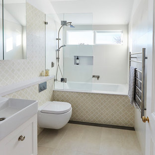 Mid-sized transitional kids bathroom in Sydney with shaker cabinets, white cabinets, an alcove tub, an open shower, a wall-mount toilet, beige tile, ceramic tile, beige walls, ceramic floors, a wall-mount sink, solid surface benchtops, beige floor, an open shower and white benchtops.