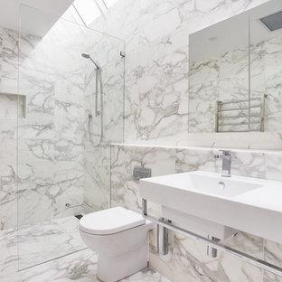 シドニーの広いコンテンポラリースタイルのおしゃれなマスターバスルーム (壁付け型シンク、バリアフリー、白いタイル、ガラス扉のキャビネット、白いキャビネット、一体型トイレ、大理石タイル、マルチカラーの壁、大理石の床、珪岩の洗面台) の写真