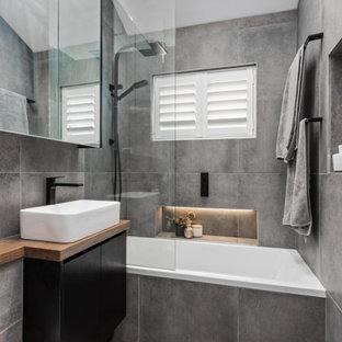 Réalisation d'une petit salle de bain principale design avec un placard à porte plane, des portes de placard noires, une baignoire posée, un combiné douche/baignoire, un WC suspendu, un carrelage gris, des carreaux de céramique, un mur gris, un sol en carrelage de céramique, une vasque, un plan de toilette en bois, un sol gris, un plan de toilette marron, une niche, meuble simple vasque, meuble-lavabo encastré et un plafond voûté.