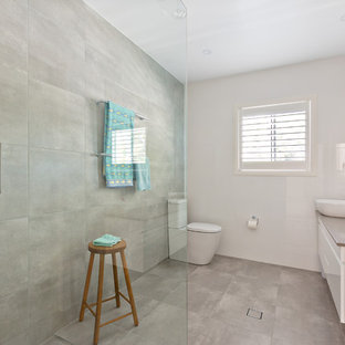 Inspiration for a beach style 3/4 bathroom in Sydney with flat-panel cabinets, white cabinets, a corner shower, a one-piece toilet, gray tile, cement tile, white walls, concrete floors, a vessel sink, grey floor, an open shower and brown benchtops.