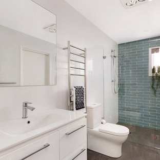 Design ideas for a mid-sized contemporary bathroom in Sydney with white cabinets, an alcove shower, a two-piece toilet, multi-coloured tile, white walls, an integrated sink, engineered quartz benchtops, brown floor, a hinged shower door and white benchtops.