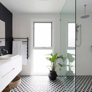 Ejemplo de cuarto de baño con ducha, actual, con armarios con paneles lisos, puertas de armario blancas, ducha a ras de suelo, baldosas y/o azulejos negros, paredes blancas, lavabo encastrado, suelo negro y ducha abierta