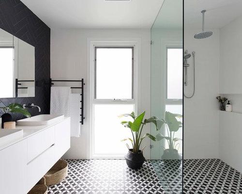Stanza da bagno con ante bianche e piastrelle nere foto idee