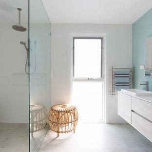 Foto de cuarto de baño con ducha, marinero, sin sin inodoro, con armarios con paneles lisos, puertas de armario de madera clara, bañera exenta, baldosas y/o azulejos azules, paredes blancas, lavabo encastrado, suelo beige y ducha abierta