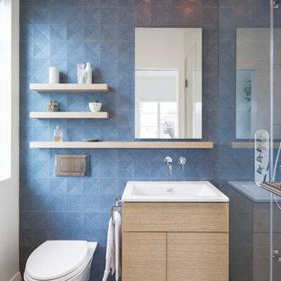 Esempio di una stanza da bagno design con ante lisce, pareti bianche, top in quarzo composito, ante in legno chiaro, doccia alcova, WC sospeso, piastrelle blu e lavabo a consolle
