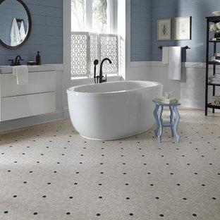 Inspiration för ett stort amerikanskt en-suite badrum, med släta luckor, vita skåp, ett fristående badkar, svart och vit kakel, blå väggar, vinylgolv, ett undermonterad handfat, bänkskiva i täljsten och beiget golv