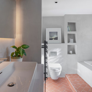 Photo of a medium sized scandi family bathroom in Oxfordshire with a built-in bath, a shower/bath combination, a wall mounted toilet, grey tiles, grey walls, ceramic flooring, a trough sink, wooden worktops, red floors, an open shower and beige worktops.
