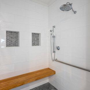 Ispirazione per una stanza da bagno padronale chic di medie dimensioni con ante con bugna sagomata, ante grigie, doccia a filo pavimento, piastrelle bianche, piastrelle in ceramica, pareti grigie, pavimento in gres porcellanato, lavabo sottopiano, top in quarzite, pavimento bianco, porta doccia a battente, top bianco, panca da doccia, un lavabo e mobile bagno incassato