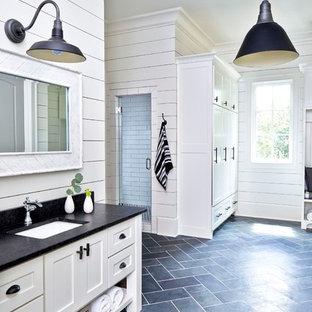 Diseño de cuarto de baño principal, campestre, extra grande, con armarios estilo shaker, puertas de armario blancas, sanitario de una pieza, baldosas y/o azulejos negros, baldosas y/o azulejos de piedra, paredes blancas, suelo de pizarra, lavabo bajoencimera y encimera de granito