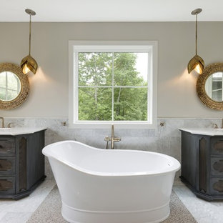 Example of a large classic master marble floor and white floor freestanding bathtub design in Minneapolis with furniture-like cabinets, gray walls, an undermount sink, quartzite countertops and dark wood cabinets