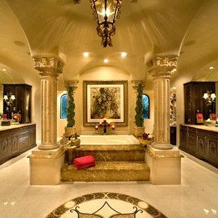Idee per un'ampia stanza da bagno padronale mediterranea con vasca idromassaggio, piastrelle beige, pareti beige, pavimento con piastrelle in ceramica, consolle stile comò, ante in legno bruno, doccia doppia, WC monopezzo, lastra di pietra, lavabo integrato e top in granito