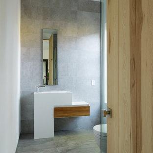ロサンゼルスの小さいコンテンポラリースタイルのおしゃれなバスルーム (浴槽なし) (ペデスタルシンク、グレーのタイル、セメントタイル、コンクリートの床、フラットパネル扉のキャビネット、淡色木目調キャビネット、コーナー設置型シャワー、分離型トイレ、グレーの壁、人工大理石カウンター) の写真