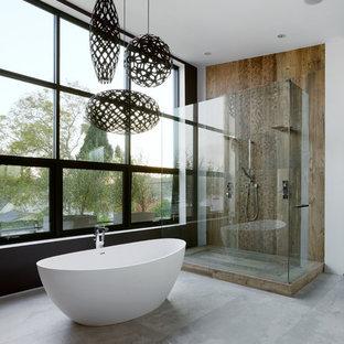На фото: с высоким бюджетом большие главные ванные комнаты в современном стиле с отдельно стоящей ванной, коричневой плиткой, бетонным полом и двойным душем
