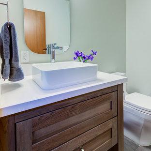 Modelo de cuarto de baño con ducha, contemporáneo, pequeño, con armarios estilo shaker, puertas de armario beige, sanitario de una pieza, paredes verdes, suelo laminado, lavabo sobreencimera, encimera de cuarzo compacto, suelo gris y encimeras blancas