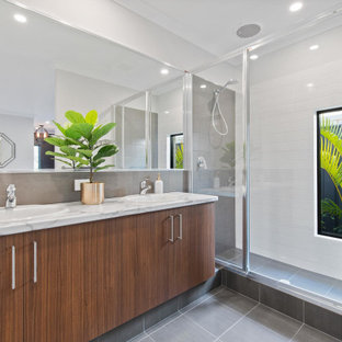 Inspiration for a contemporary bathroom in Perth with flat-panel cabinets, medium wood cabinets, an alcove shower, white tile, an undermount sink, grey floor, a hinged shower door, white benchtops and a double vanity.