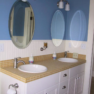 Inspiration for a mid-sized timeless yellow tile and ceramic tile mosaic tile floor bathroom remodel in Wichita with white cabinets, blue walls, tile countertops, recessed-panel cabinets and a drop-in sink