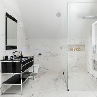 Modelo de cuarto de baño principal, contemporáneo, extra grande, con armarios tipo mueble, puertas de armario negras, sanitario de pared, baldosas y/o azulejos blancos, baldosas y/o azulejos de mármol, paredes blancas, suelo de mármol, encimera de acrílico, suelo blanco, encimeras negras y ducha esquinera