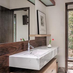 Imagen de cuarto de baño retro con armarios con paneles lisos, puertas de armario de madera clara, paredes blancas, suelo de baldosas tipo guijarro, lavabo bajoencimera, suelo gris y encimeras grises