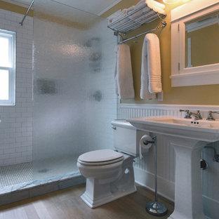 Idéer för mellanstora amerikanska badrum med dusch, med vita skåp, en öppen dusch, vit kakel, keramikplattor, beige väggar, ett piedestal handfat, en toalettstol med separat cisternkåpa, ljust trägolv, beiget golv och med dusch som är öppen