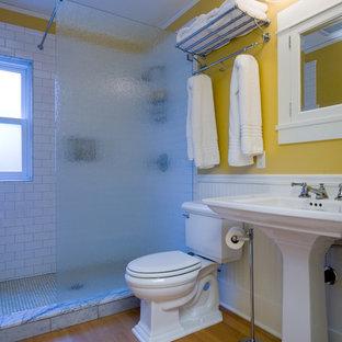 Imagen de cuarto de baño principal, tradicional, de tamaño medio, con ducha abierta, sanitario de dos piezas, baldosas y/o azulejos blancos, baldosas y/o azulejos de cemento, paredes amarillas, suelo de madera clara y lavabo con pedestal