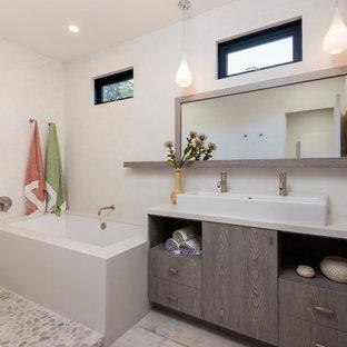 Modelo de cuarto de baño actual con armarios con paneles lisos, puertas de armario grises, bañera encastrada sin remate, ducha abierta, paredes beige, lavabo de seno grande, suelo gris y ducha abierta